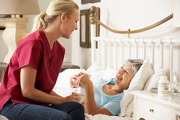 im gespräch mit gesundheit besucher zu senior frau patient im bett - hospiz stock-fotos und bilder