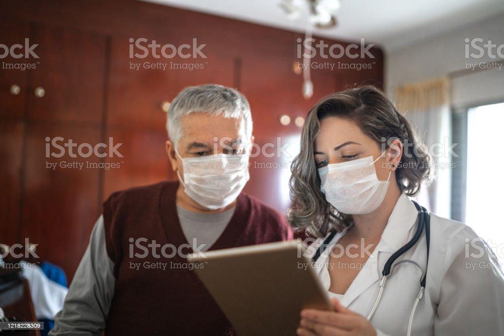 De bezoeker van de gezondheid die digitale tablet gebruikt en aan een hogere mens tijdens huisbezoek spreekt - Royalty-free 65-69 jaar Stockfoto
