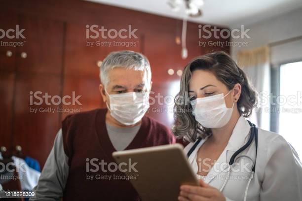 De Bezoeker Van De Gezondheid Die Digitale Tablet Gebruikt En Aan Een Hogere Mens Tijdens Huisbezoek Spreekt Stockfoto en meer beelden van 65-69 jaar