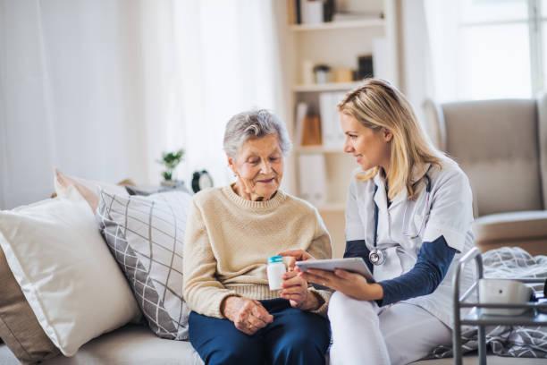 gość zdrowia z tabletem wyjaśniający starszej kobiecie, jak brać tabletki. - dojrzały zdjęcia i obrazy z banku zdjęć