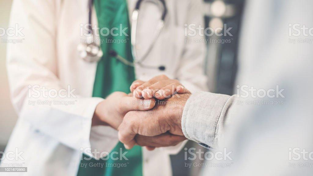 Hälsoarbetare håller patientens hand - Royaltyfri Besök Bildbanksbilder