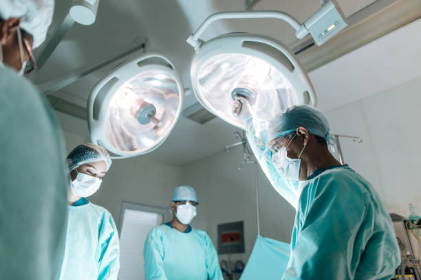 Health workers wearing surgery clothes in operation room stock photo