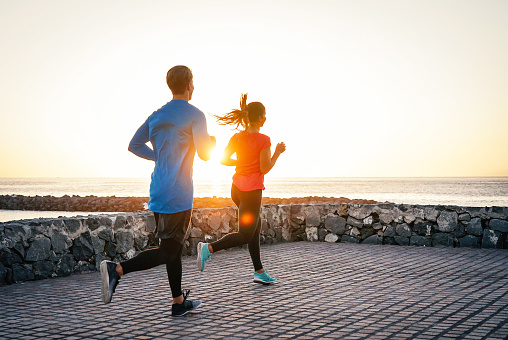 Health young couple jogging together next the ocean during a magnificent sunset - People work out on the beach - Relationship, sport, lifestyle concept