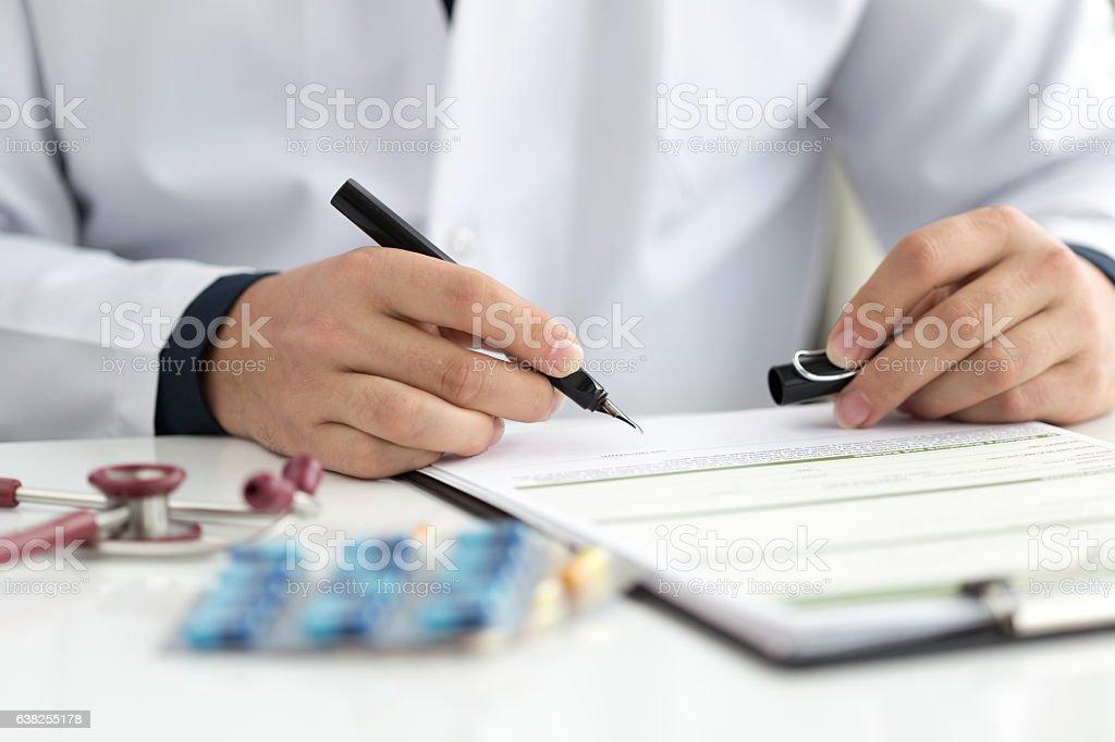 Doctor hands filling patient registration form.