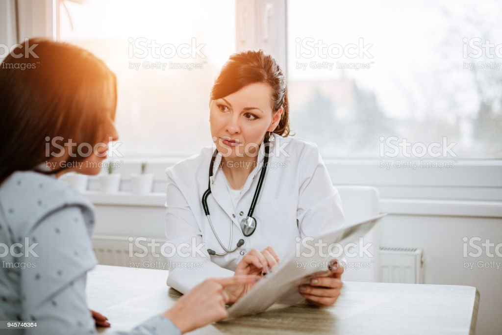 Healthcare and medicine concept. Beautiful female doctor explaining results to her patient. stock photo