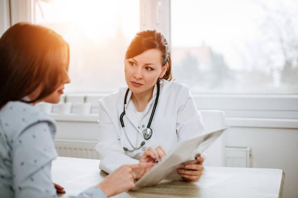 의료 및 의학 개념입니다. 아름 다운 여성 의사가 그녀의 환자에 게 결과 설명입니다. - 처방전 문서 뉴스 사진 이미지