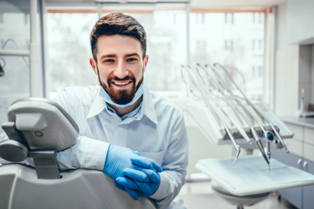 Healthcare and medicine concept. Front view of professional male dentist in white doctor coat and protective gloves sitting in dental chair and equipment, looking at camera and smiling. Bearded man posing during working process. dentist stock pictures, royalty-free photos & images
