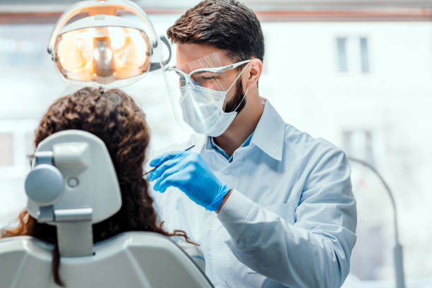Healthcare and medicine concept. Dentist working in dental clinic with patient in the chair. protective workwear stock pictures, royalty-free photos & images