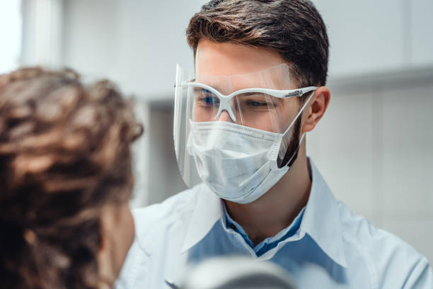 Healthcare and medicine concept. Man dentist at work with patient. At the dentist office, examination. protective face mask stock pictures, royalty-free photos & images