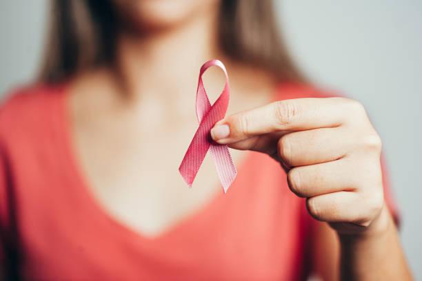 saúde e conceito da medicina-mulher que prende a fita cor-de-rosa do cancro da mama - outubro rosa - fotografias e filmes do acervo