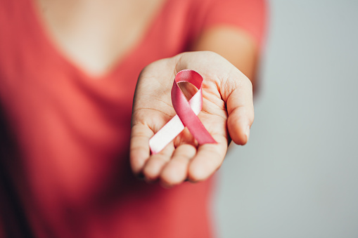istock Healthcare and medicine concept - woman holding pink breast cancer awareness ribbon 1170403890