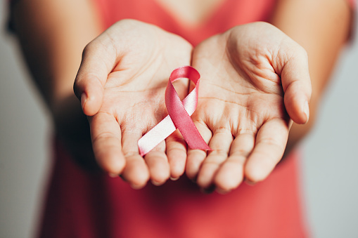 istock Healthcare and medicine concept - womans hands holding pink breast cancer awareness ribbon 1170403911