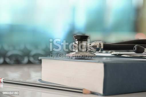 healthcare and medicine concept. Stethoscope with medical text book on doctor student desk at classroom in the hospital.
