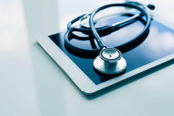 Concepto de salud y tecnología-tableta y estetoscopio sobre mesa blanca - foto de stock