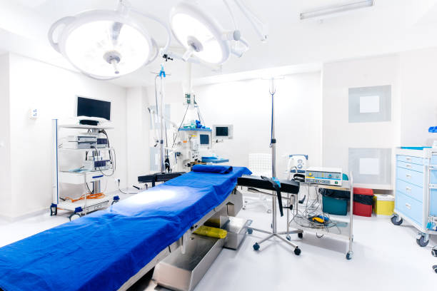 Healthcare center, hospital room. Interior of operating room with empty bed and lamps stock photo