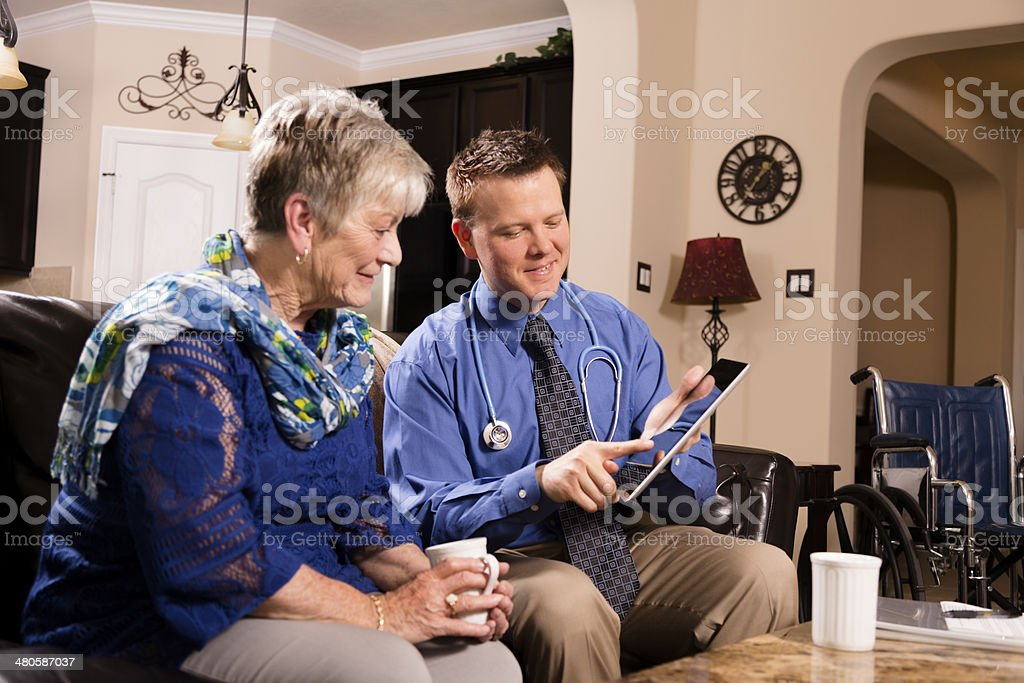 Healthcare: Concierge doctor visits senior woman at home. stock photo