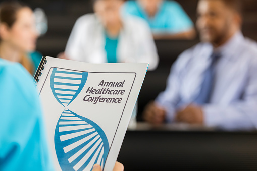 istock Healthcare conference attendee holds conference booklet 986274904