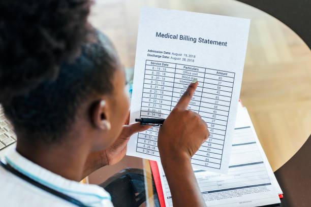 gezondheidskosten en vergoedingen concept. hand van slimme arts berekenen van medische kosten in moderne ziekenhuis. arts het invullen van een medisch claim formulier door stethoscoop - snavel stockfoto's en -beelden