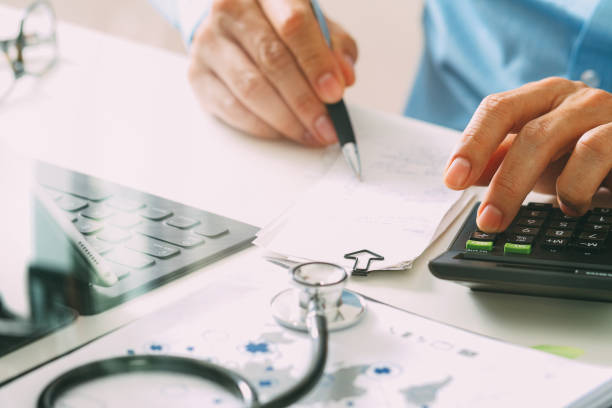 Healthcare costs and fees concept.Hand of smart doctor used a calculator for medical costs in modern hospital Healthcare costs and fees concept.Hand of smart doctor used a calculator for medical costs in modern hospital fee stock pictures, royalty-free photos & images