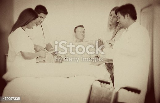 Caring hospital staff check on patient in hospital. Asian doctor using digital tablet.  Wife with husband patient in background as nurses check his chart. Sepia toned.