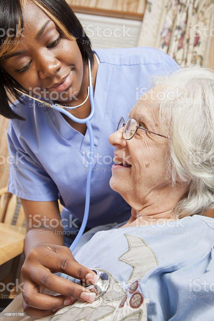Healthcare: Home health nurse examines senior patient. stock photo