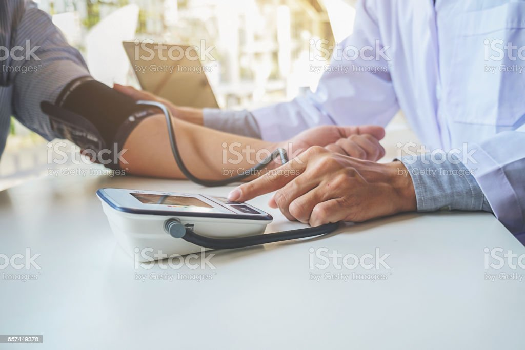 healthcare, hospital and medicine concept - doctor and patient measuring blood pressure. stock photo
