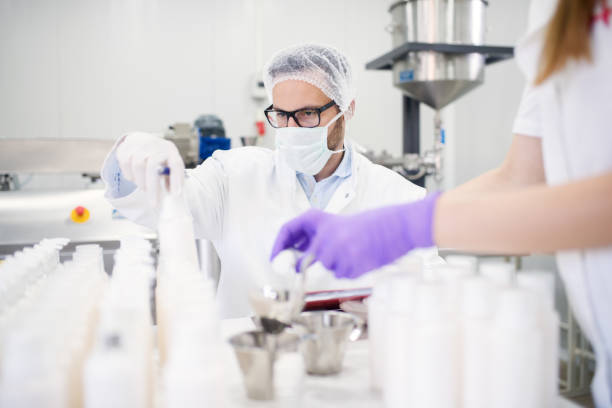 Healthcare industry. Creme production. Working in laboratory with special equipment. Checking creme quality at healthcare industry. stock photo