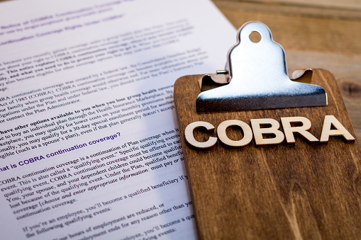COBRA Healthcare Insurance Benefits for Unemployment concept on wooden board