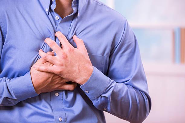 Saúde: Homem segurando o peito na dor, possível ataque cardíaco. - foto de acervo