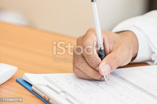 Healthcare medical Expenses concept, Hands Doctor's writing and working on prescription clipboard with record information paper folders on desk in hospital or clinic. Selective focus