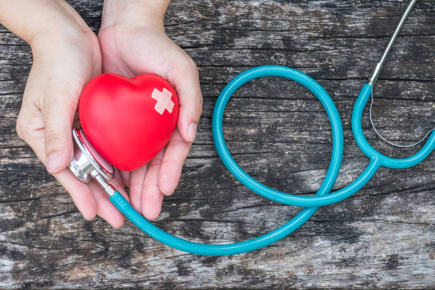 healthcare medical insurance business and world heart health day concept with red heart on woman's hands support with doctor's stethoscope - luogo d'interesse nazionale foto e immagini stock