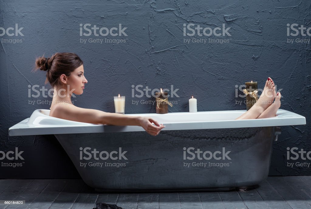 Healthcare & Medicine Beautiful woman relaxing in bathtub with lighted candles Retro old style bathroom Beauty & Wellness stock photo