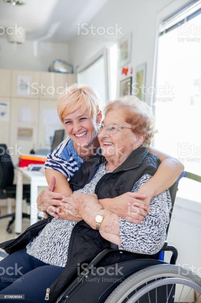 Healthcare Nurse Embracing Senior Woman in the Retirement Home