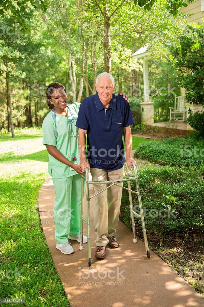 Healthcare: Nurse helps senior man outside using walker. Nursing home. stock photo