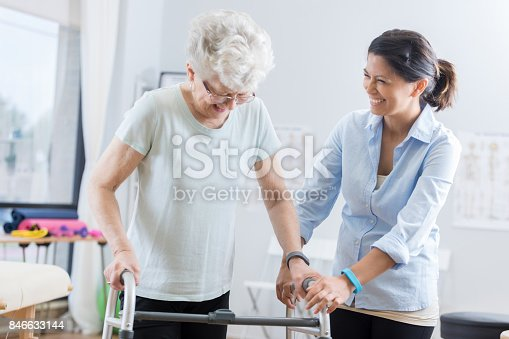950649706istockphoto Healthcare professional helps senior woman walk with a walker 846633144