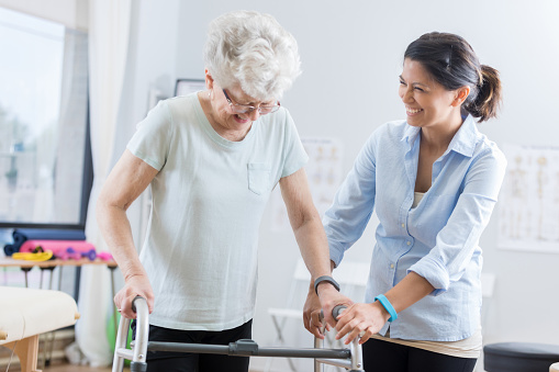 950649706 istock photo Healthcare professional helps senior woman walk with a walker 846633144