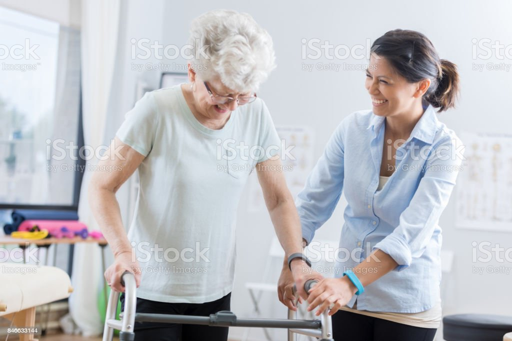 Healthcare professional helps senior woman walk with a walker stock photo