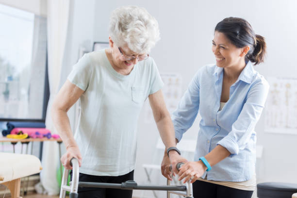 healthcare professional helps senior woman walk with a walker - recovery stock pictures, royalty-free photos & images