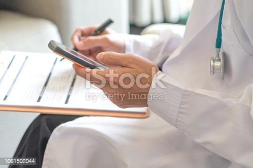 istock Healthcare professional medical doctor using tablet and smartphone for consult patient via online: Physician working tele-consultation: Hospital e-healthcare professionalism Digital health concept. 1061502044