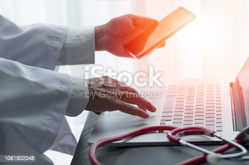 istock Healthcare professional medical doctor using tablet and smartphone for consult patient via online: Physician working tele-consultation: Hospital e-healthcare professionalism Digital health concept. 1061502048