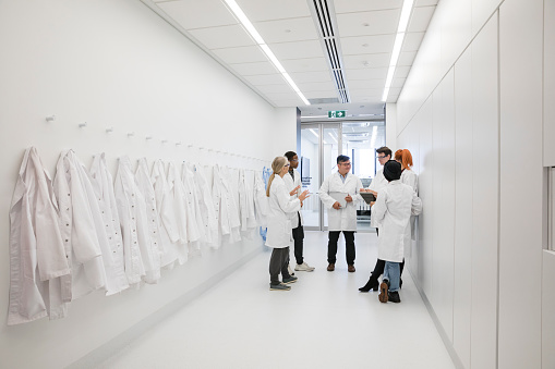 Medical protective clothing hanging in a hallway. A team of medical scientist gather around talking
