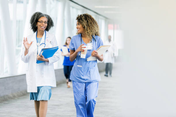 Healthcare professionals walk in hospital hallway Mature female doctor gestures while walking in hospital skybridge with female nurse. She is carrying a patient's chart. The nurse is holding a coffee cup. female doctor stock pictures, royalty-free photos & images