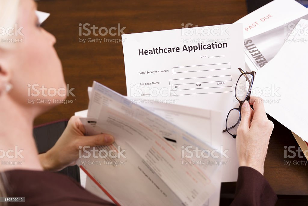 Healthcare: Woman fills out health insurance application. royalty-free stock photo