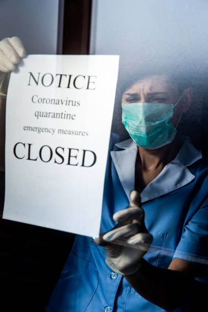 Healthcare worker attaching Closed sign notice for epidemic Coronavirus on window stock photo