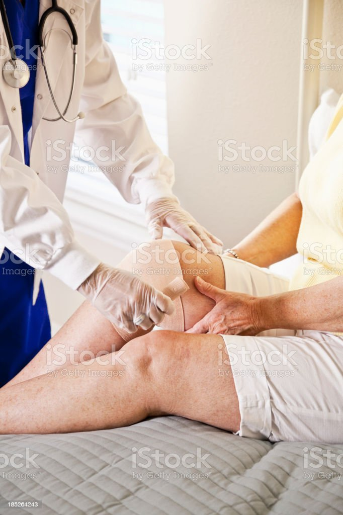 Healthcare worker bandaging patient's knee royalty-free stock photo