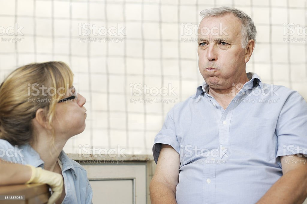 Healthcare worker checking man's swallowing power stock photo