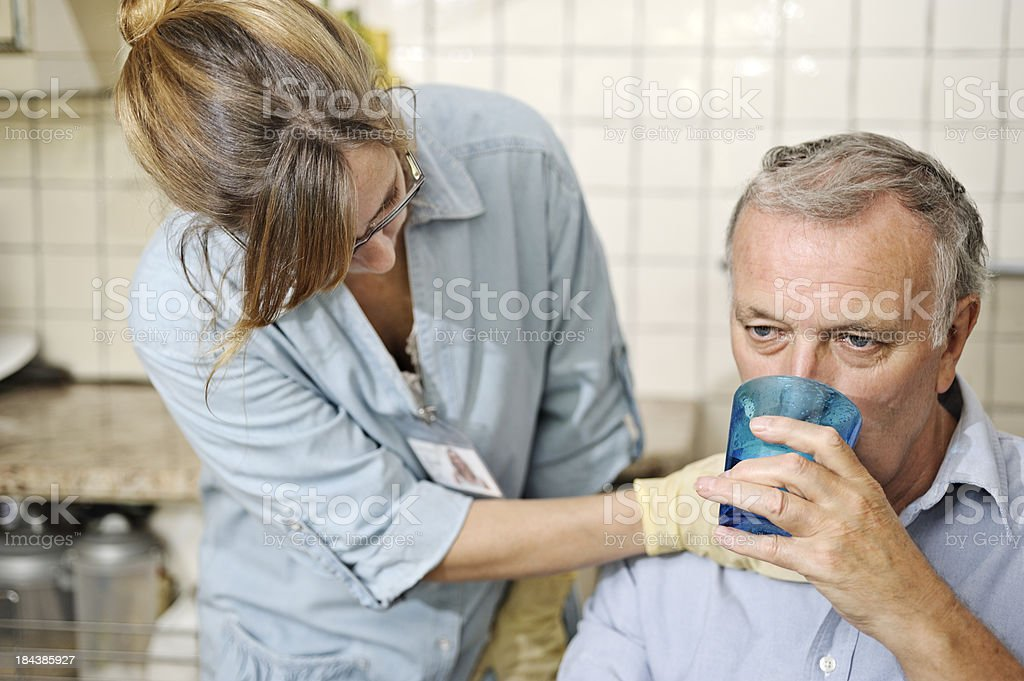 Healthcare worker checking man's throat stock photo