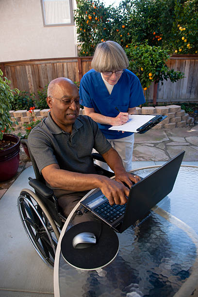 Healthcare worker helping disabled senior stock photo