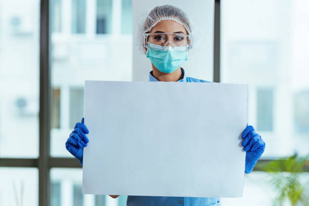 Healthcare worker holding blank placard in the hospital. stock photo