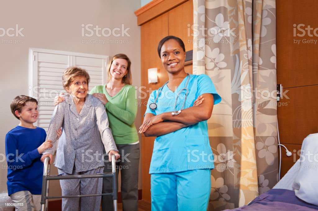 Healthcare worker in hospital room with senior patient and famil royalty-free stock photo